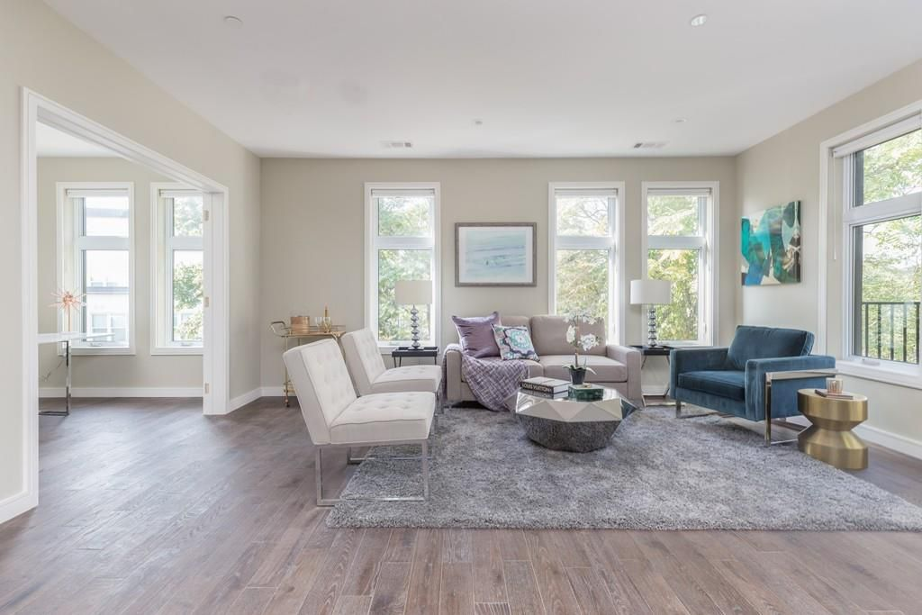 A spacious, sunny living room with furniture and next to a large opening.