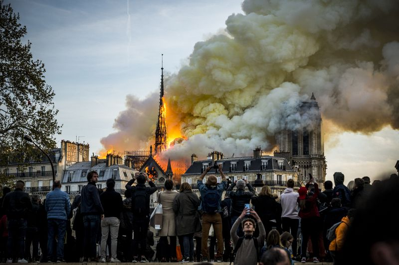 People watch the landmark Notre Dame Cathedral burning in central Paris on April 15, 2019.