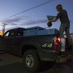 In this photo made Thursday, March 23, 2012, a buyer squeezes water from a net of elver while emptying a tank on the back of fisherman's truck in Portland, Maine.  The baby eels are fetching the fishermen more than $2,000 per pound this year.