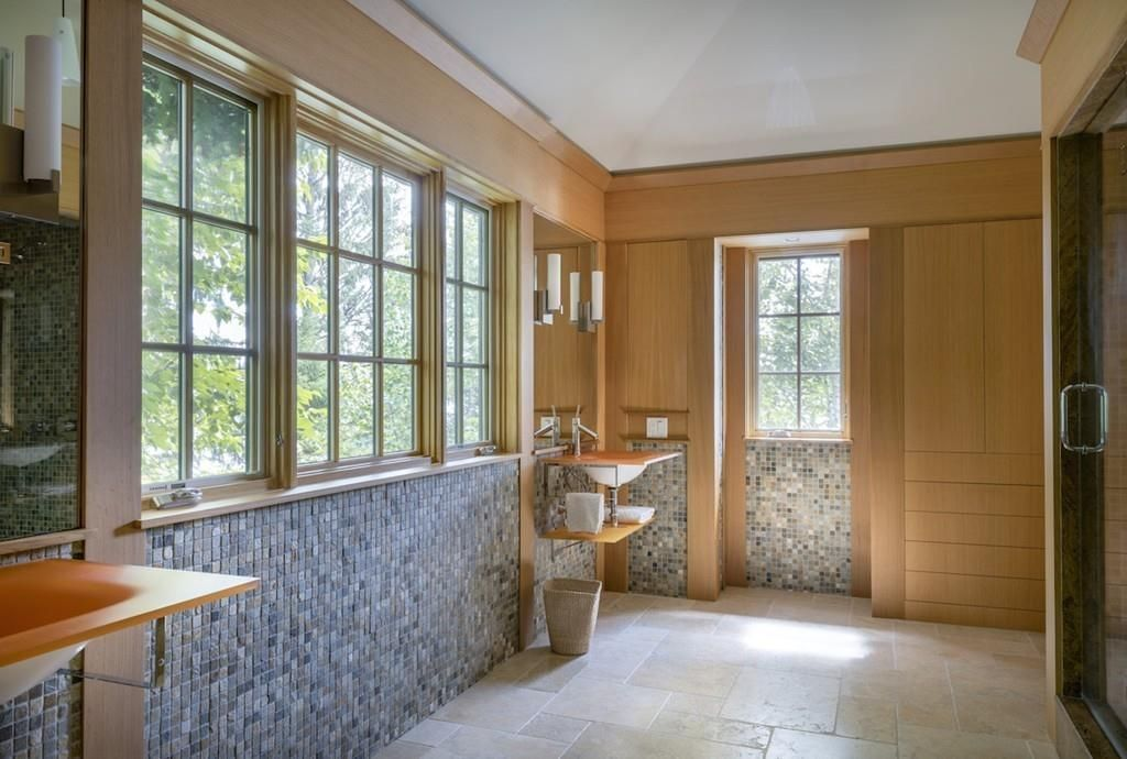 A spacious bathroom with three windows separating two sinks, and a shower is just beyond the sinks.