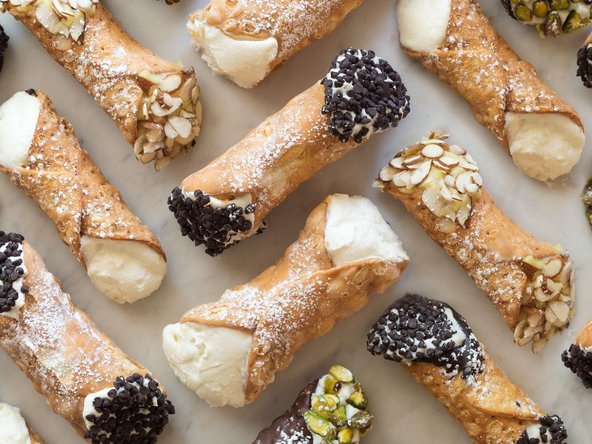 A zig-zag pattern of cannoli from Mike's Pastry and Modern Pastry, arranged on a white background. Some are garnished with chocolate chips or pistachios.