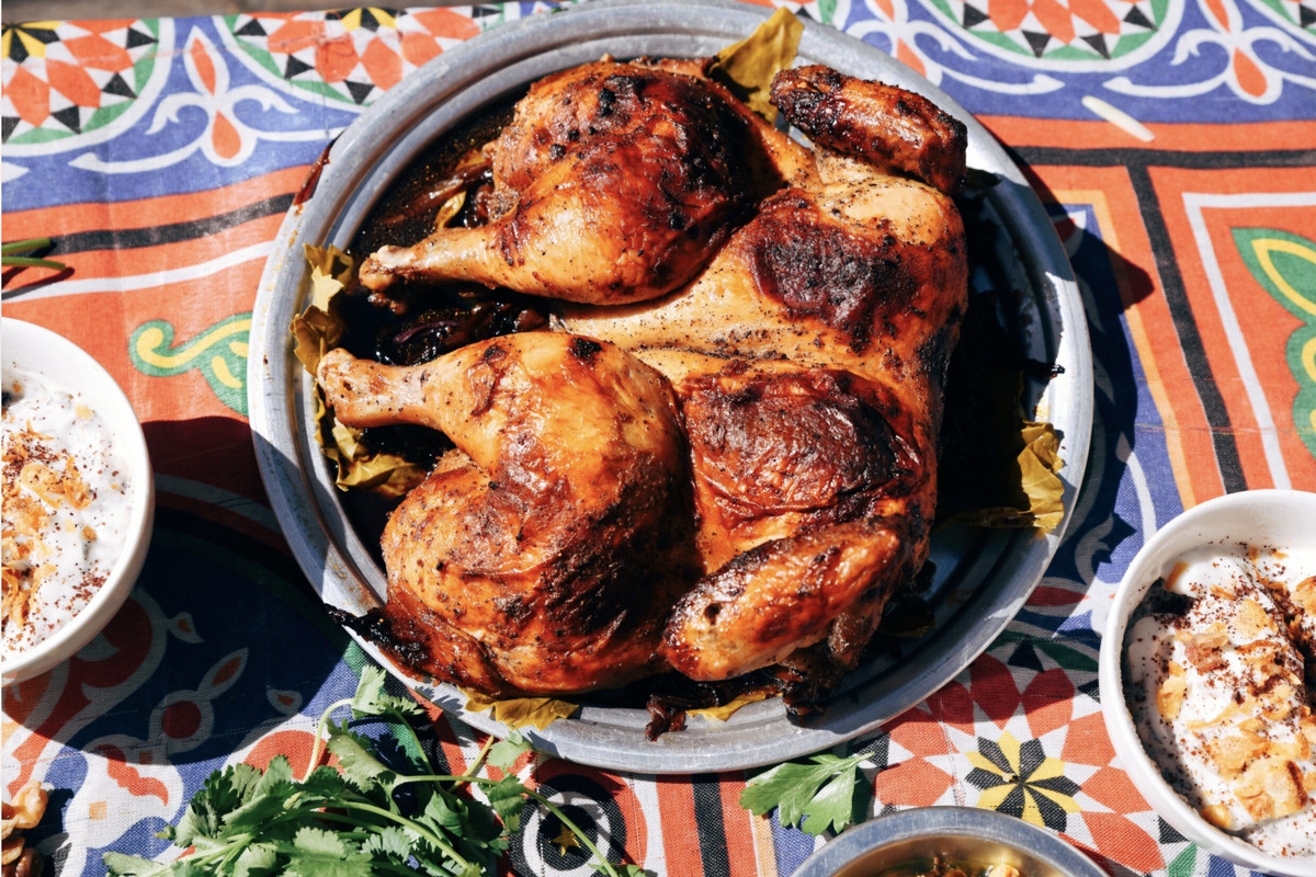 A big bowl of roasted chicken sits on a colorful tablecloth.