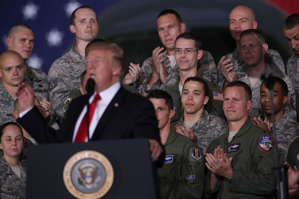 President Trump speaks at a podium in front of a crowd of Air Force personnel.