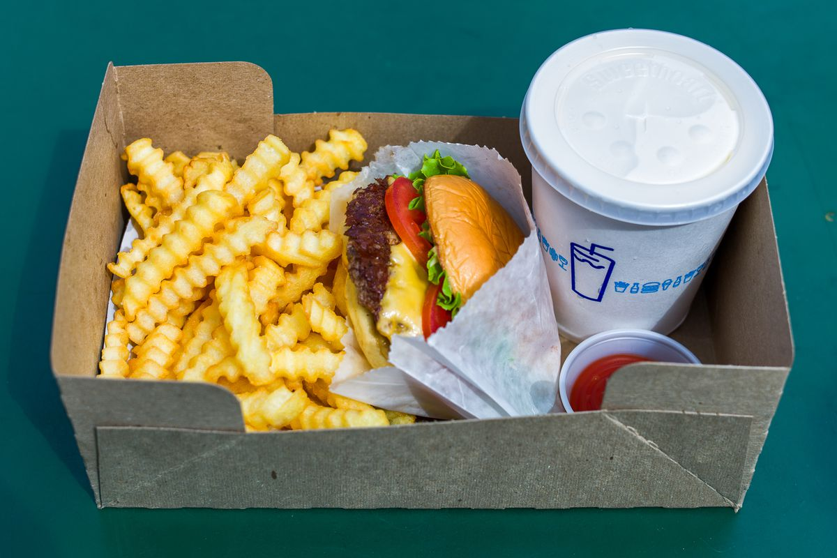 A Shake Shack burger, crinkle fries, and a drink in a paper box
