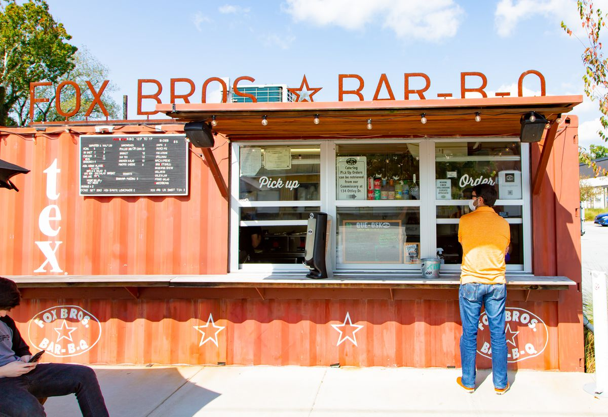 An orange container houses Fox Bros. Bar-B-Q with its name in metal orange lettering above the container. A man in an orange shirt and jeans wearing a mask orders at the to-go window