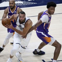 Utah Jazz center Rudy Gobert (27) gets ready to shoot in front of Phoenix Suns guard Jevon Carter (4) and Phoenix Suns center Damian Jones (30) during a preseason NBA game at the Vivint Smart Home Arena in Salt Lake City on Monday, Dec. 14, 2020. The Jazz beat the Suns 111-92.