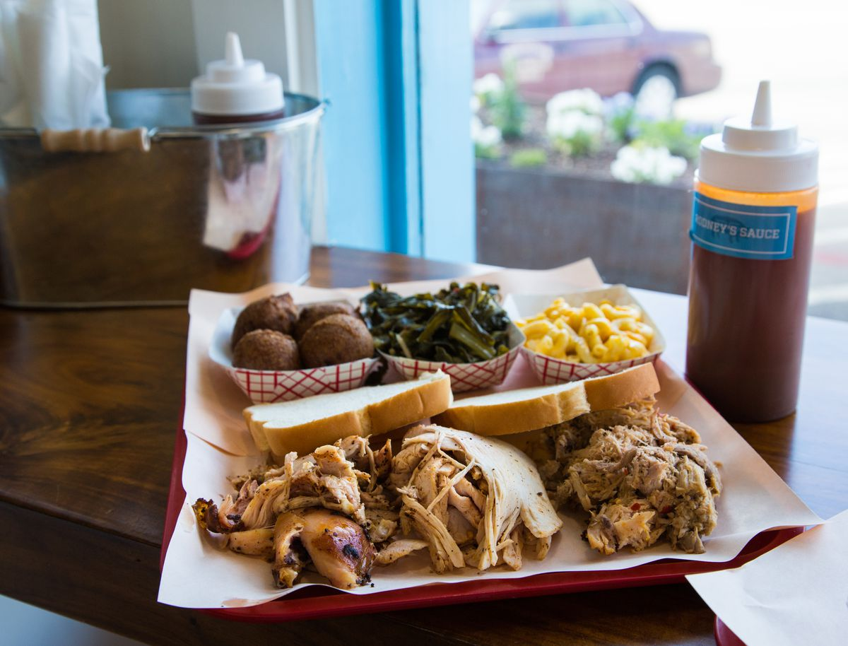 A tray of chopped barbecue pork and chicken, hushpuppies, collards, and mac and cheese