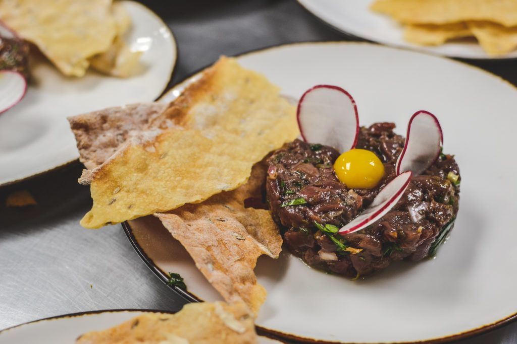 Tartare on a white plate with a quail egg on top