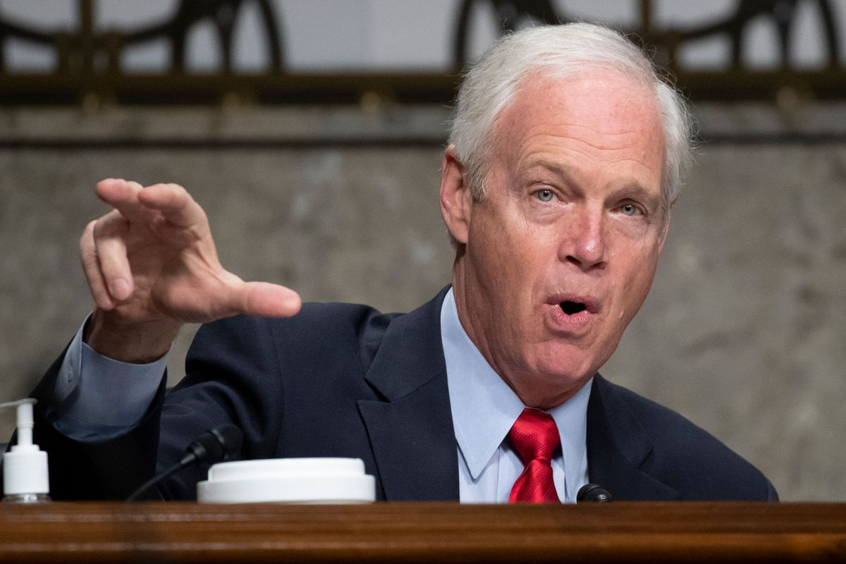 Johnson, in a navy suit, blue shirt, and red tie, raises his left hand, while speaking emphatically. Clean shaven, and with his white hair combed back, he sits at a desk.