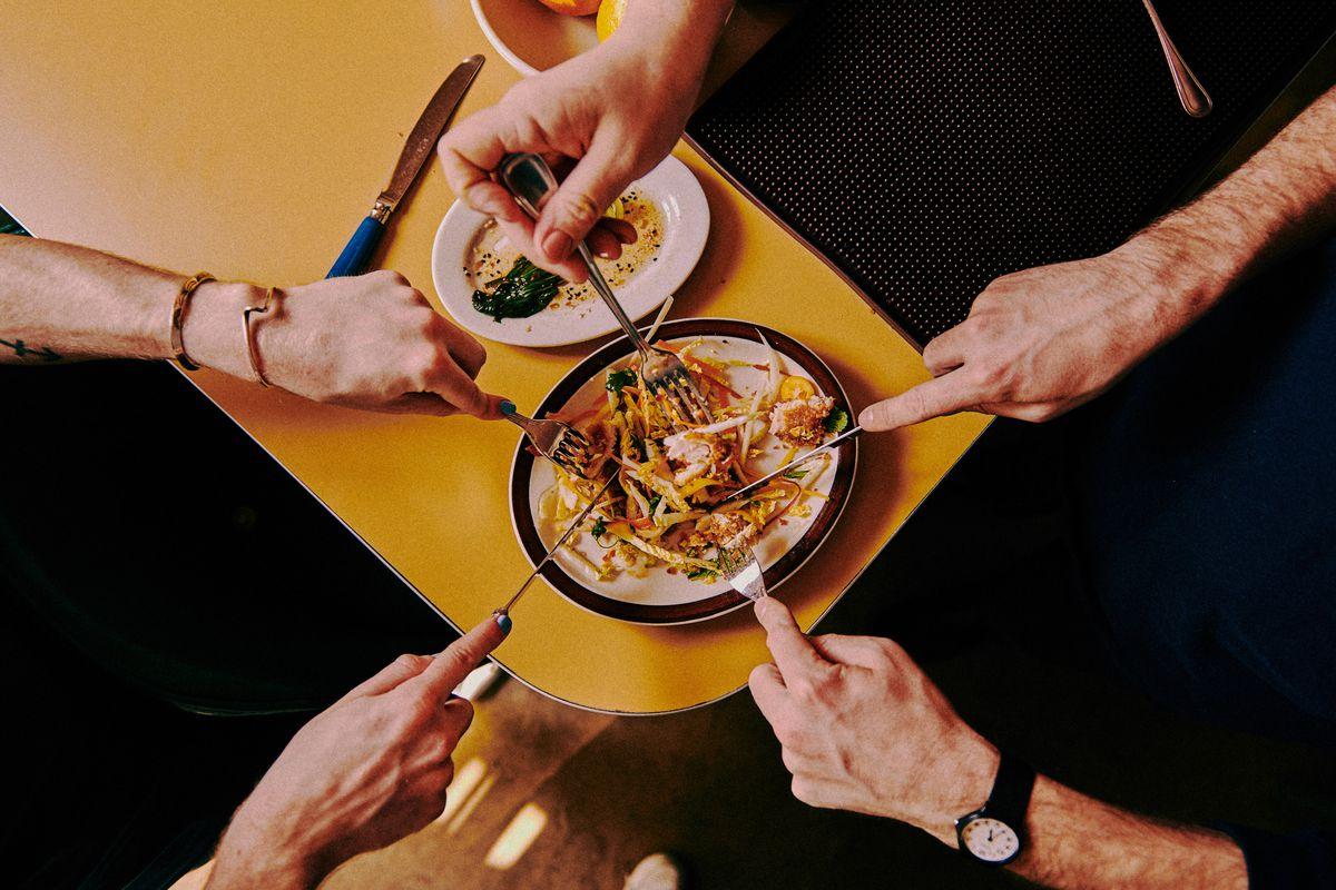 Five hands use forks to taste a dish at Meme's Diner