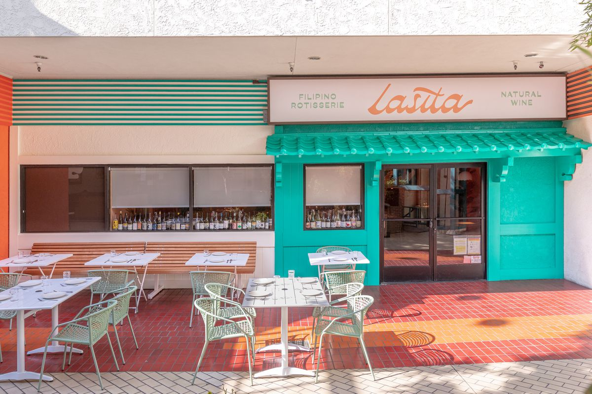 An outdoor patio seating area in front of a light teal and orange restaurant facade.
