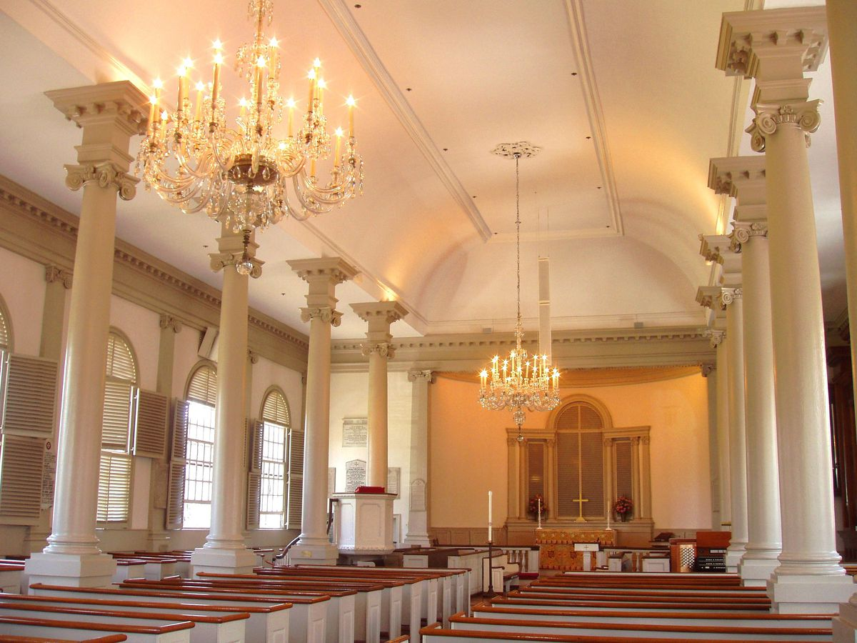 The interior of a church with arched ceilings, a single aisle, pews on either side of the aisle, and the aisle leading to an altar.