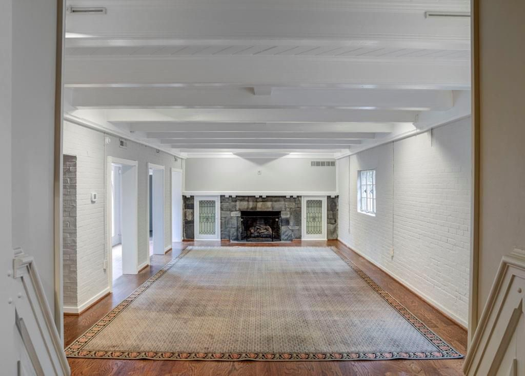 A long white room with wood and a carpet in a basement.