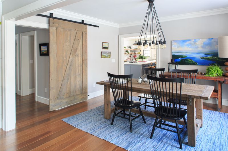 A dining room with four high back black chairs, and exposed light fixture and a sliding barn door that leads to a hallway.