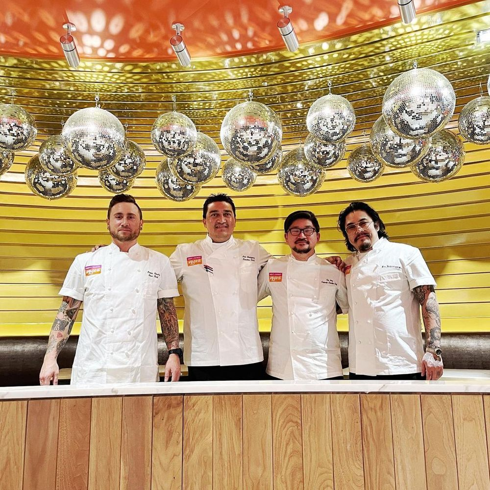 Four men in chef's coats stand under a canopy of disco balls