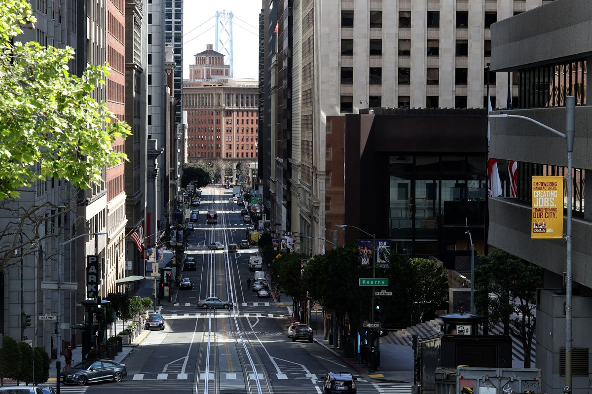A street with no cars on it, flanked on both sides by tall buildings.