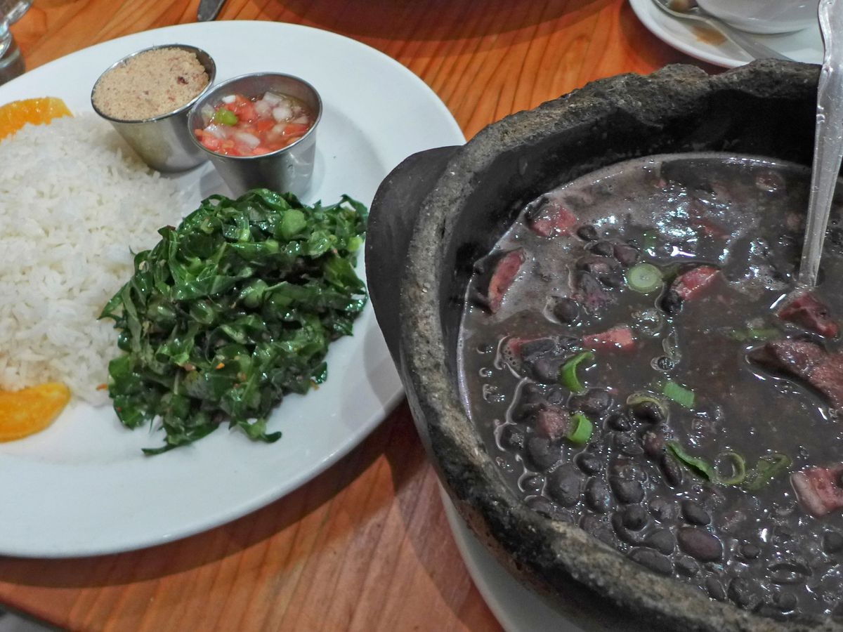 A cauldron of black beans on the right, a plate of rice, shredded kale, toasted manioc meal, and orange segments on the left...