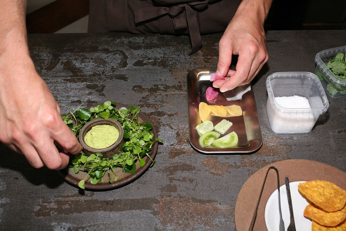 Plating a snack of pistachio and pine oil mole, corn crisp, and crudités, Santiago Lastra's replacement for guacamole at Kol