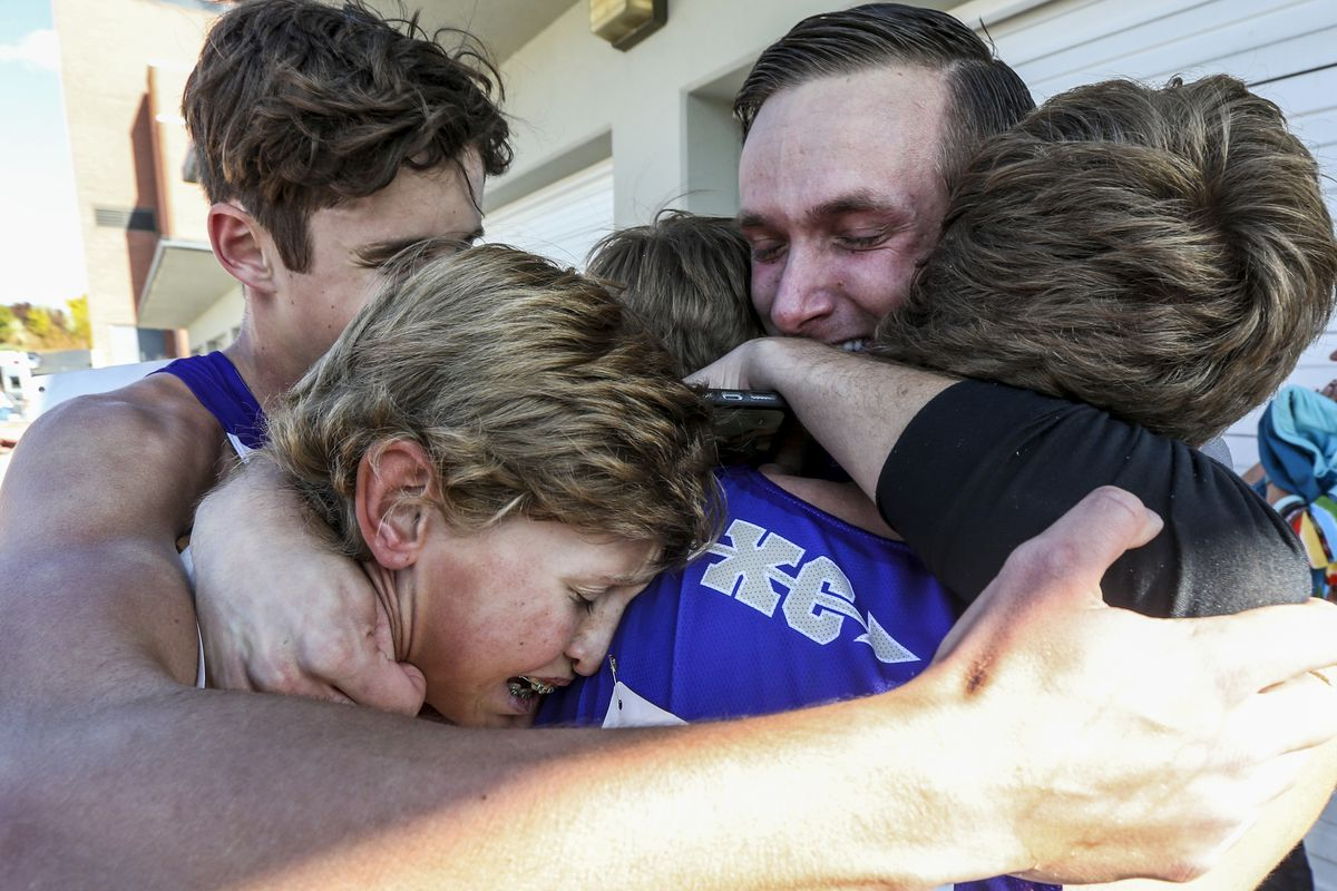Wayne High School's cross-country runners embrace after discovering they won their first ever state championship during the 1A State Cross-Country Championships at Sugar House Park and Highland High School in Salt Lake City on Wednesday, Oct. 23, 2019.
