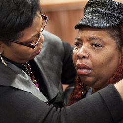 Dell Taylor, right, is comforted by the Rev.Traci Blackmon, a member of the Ferguson Commission appointed by Missouri Gov. Jay Nixon, during the opening meeting of the commission at the Ferguson Community Center in Ferguson, Mo. Monday, Dec. 1, 2014.  The 16-person panel was chosen by Missouri's governor to help find long-term solutions after the Ferguson police shooting of an unarmed man.