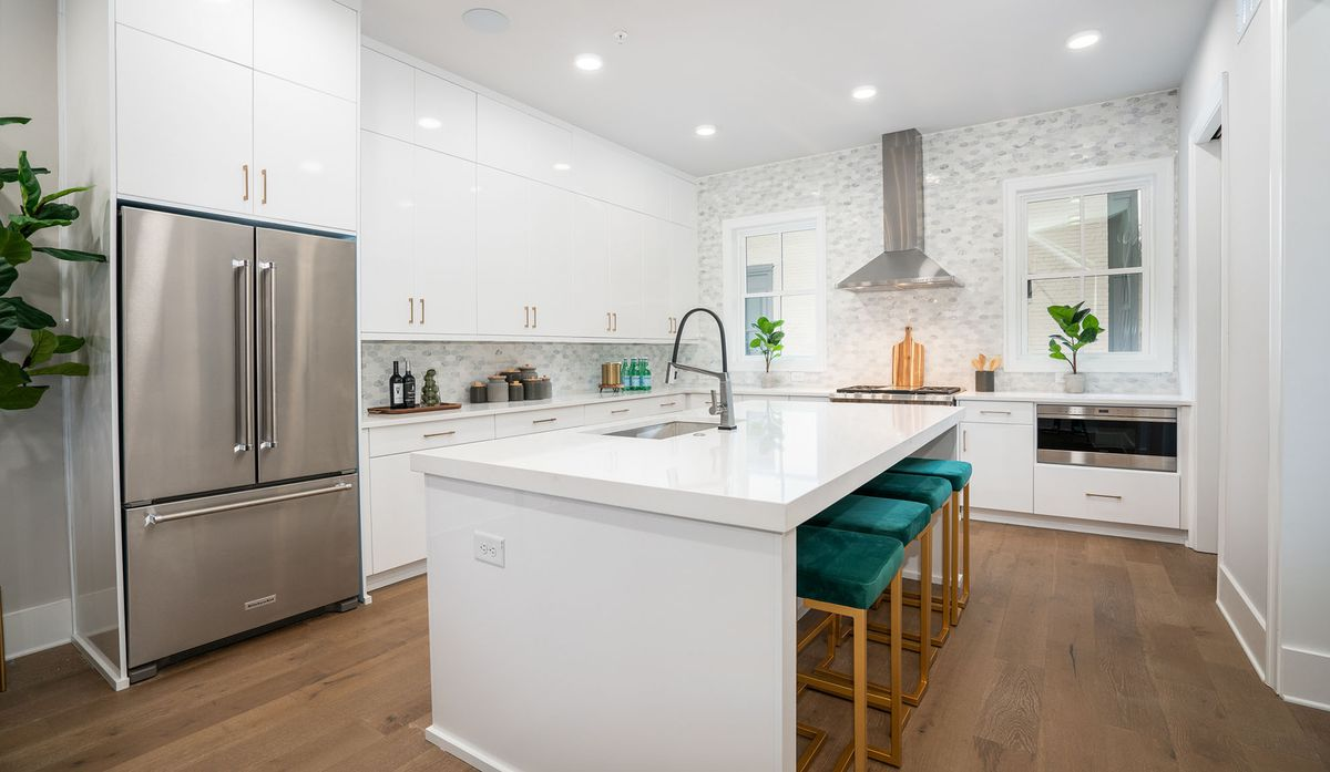 A big white kitchen with wood floors and stainless appliances.