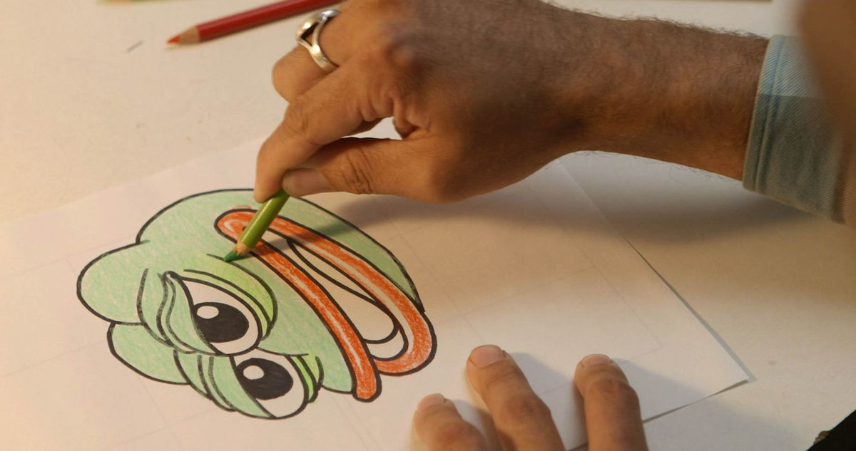 a man's hand uses a green colored pencil to shade a drawing of pepe the frog in the documentary Feels Good Man
