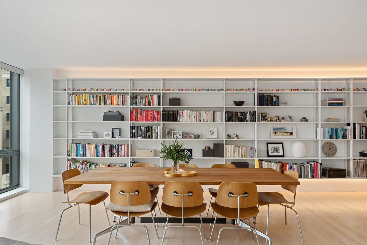 A wood dining table surrounded by eight chairs in front a wall of floor-to-ceiling built-in bookshelves.