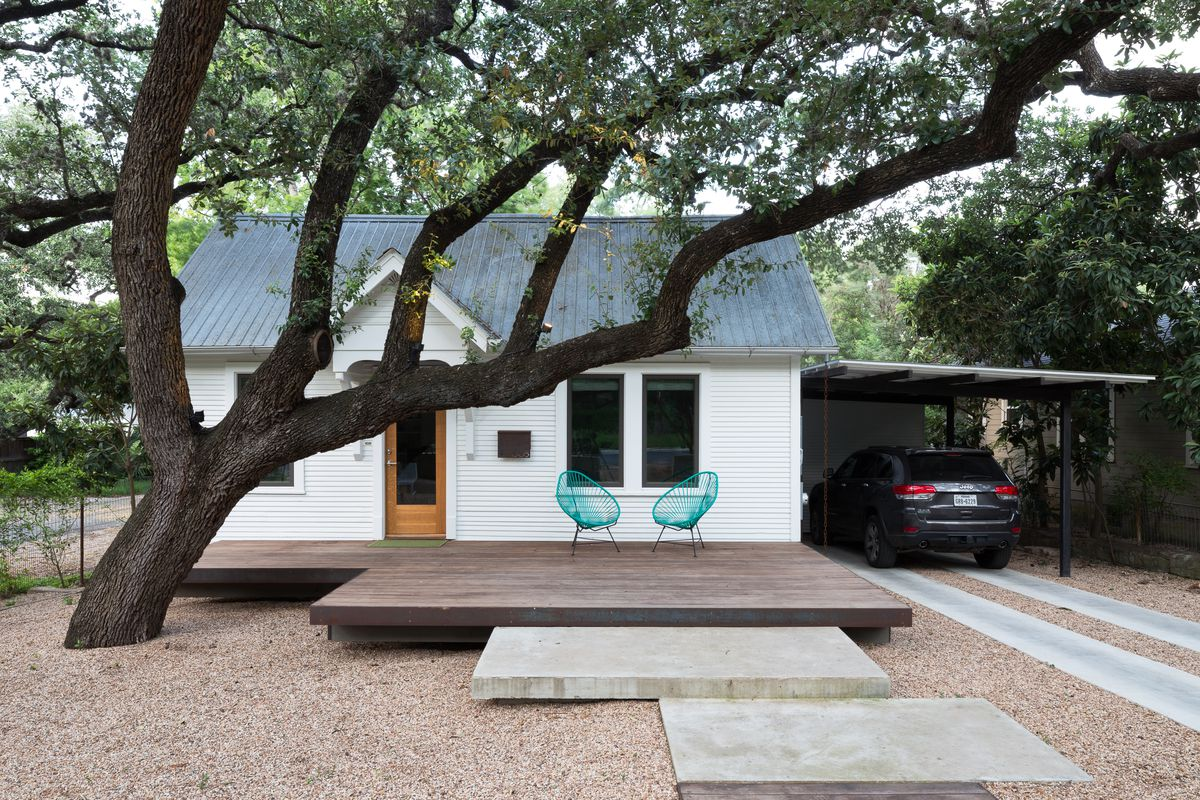 Small white wooden bungalow with minimalist landscaping