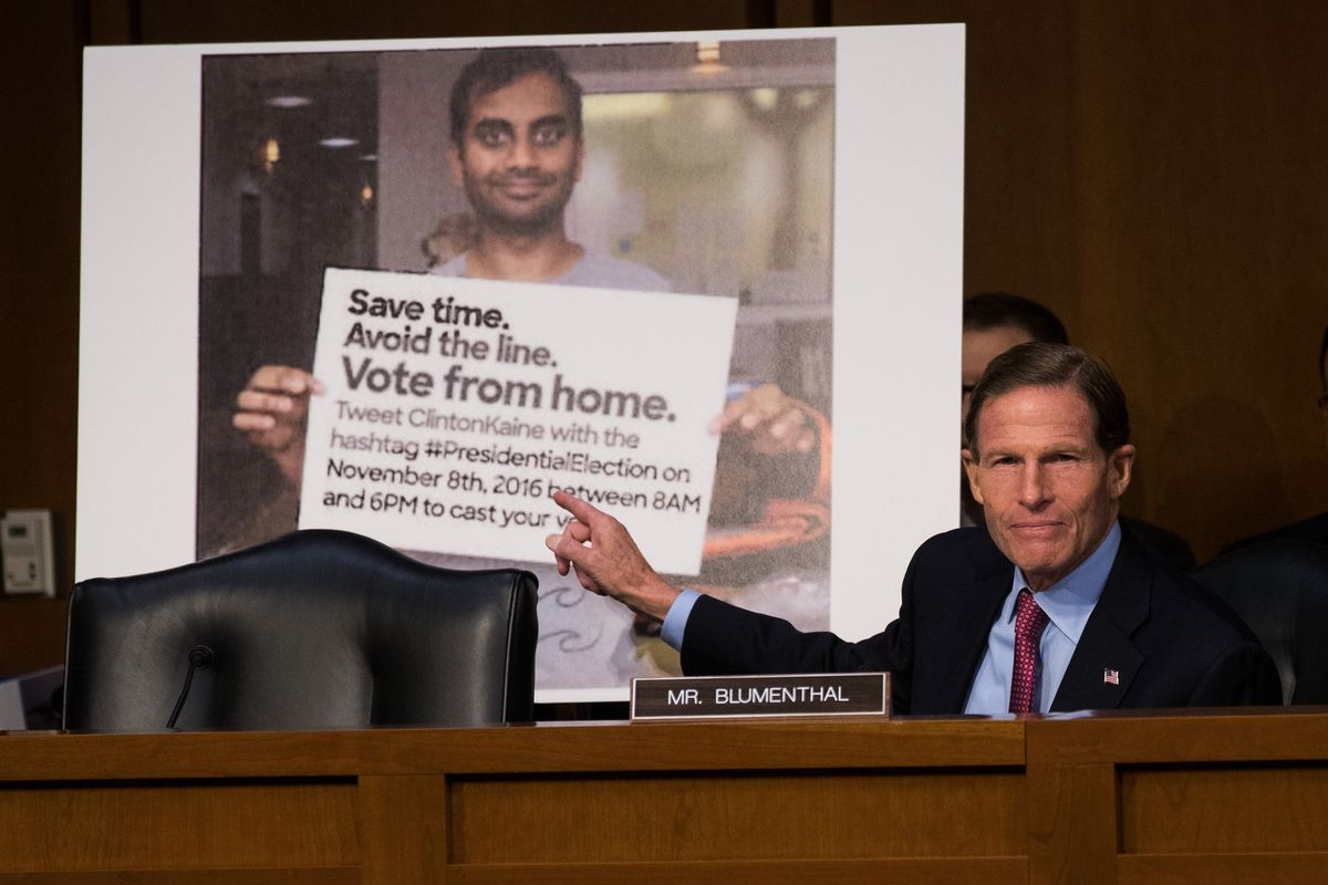 A lawmaker pointing to a tweet including a photo of Aziz Ansari with a sign saying people can vote from home via text message