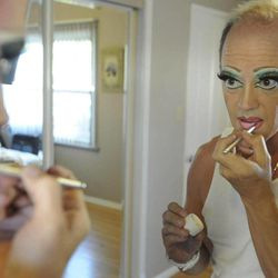 This Friday, Aug. 5, 2011 photo shows Kevin Farrell as he applies makeup in a dressing room while transforming into his alter personality Dee W. Ieye before throwing a Tupperware party in Bellflower, Calif. Tupperware, it seems, is enjoying a renaissance 65 years after it first hit the market with Wonder Bowls, Bell Tumblers and Ice-Tup molds for homemade frozen treats.