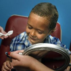 Kamden Gill, who is 5 years old, looks at himself in a mirror after having his bandages removed by Dr. Steven Mobley at the Surgical Specialty Center in Salt Lake City on Friday, Sept. 23, 2011. Mobley performed an otoplasty to fix Kamden's protruding ears.