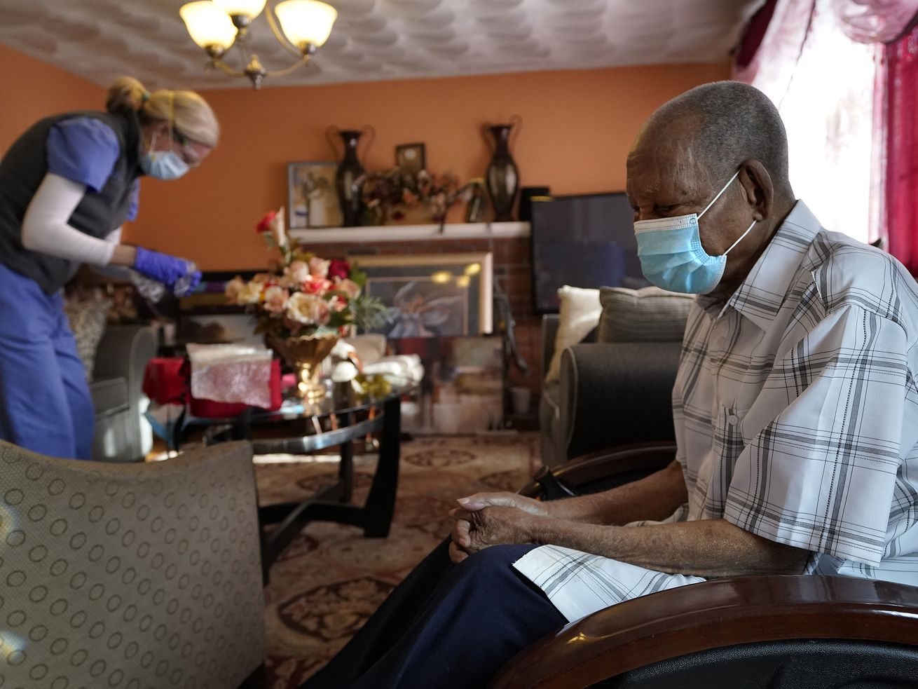In this Feb. 11, 2021, file photo Edouard Joseph, 91, right, clasps his hands as geriatrician Megan Young, left, prepares to give him a COVID-19 vaccination at his home in the Mattapan neighborhood of Boston.