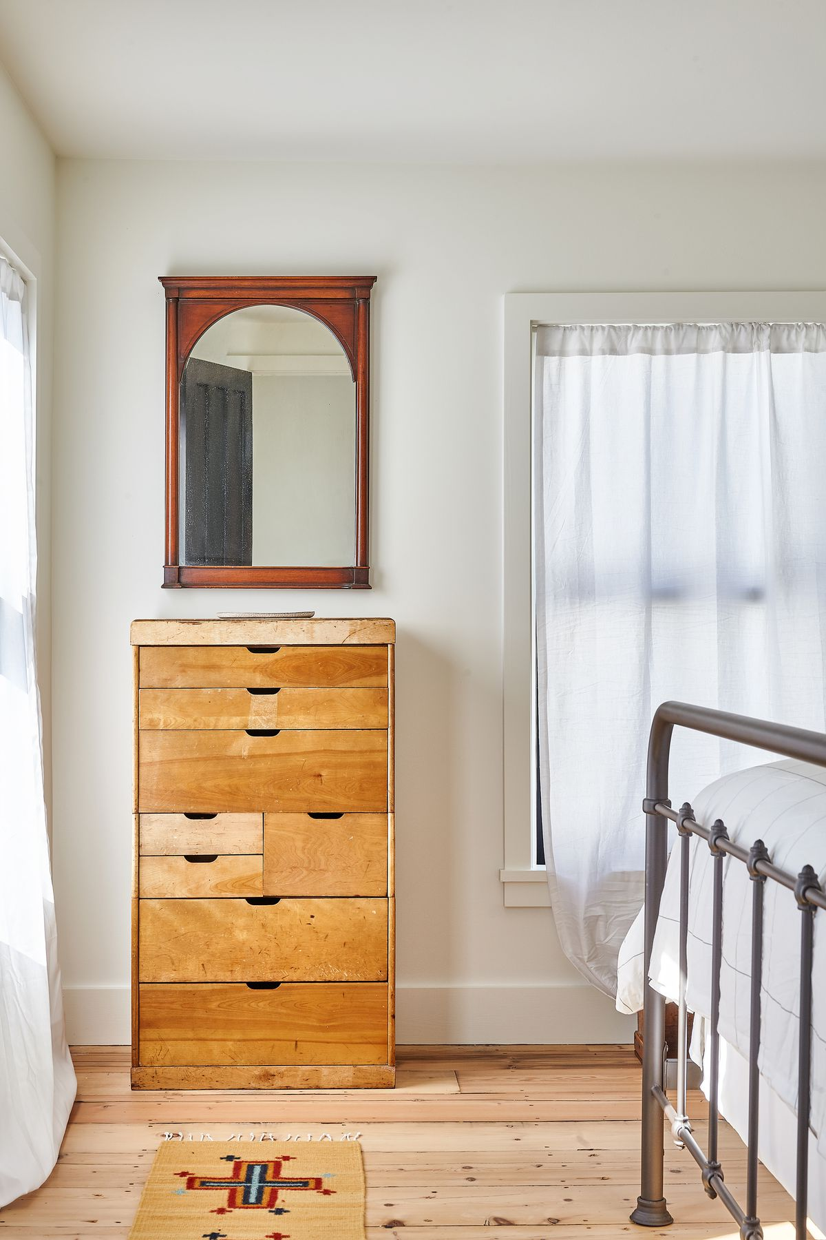 A bedroom contains a vintage wood dresser with a mirror hanging over it.