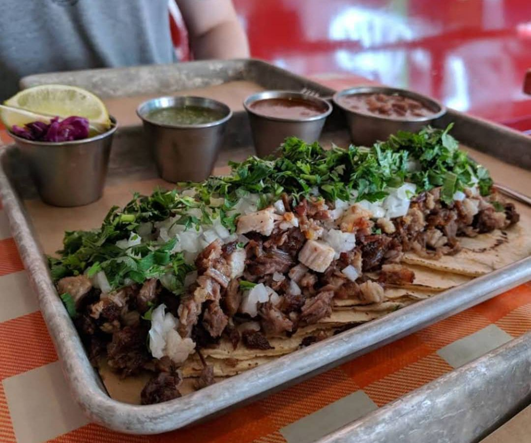 Layers of meat, diced onions, and cilantro lay across several tortillas on a steel tray with small metal cups of salsa, beans, and lemon wedges