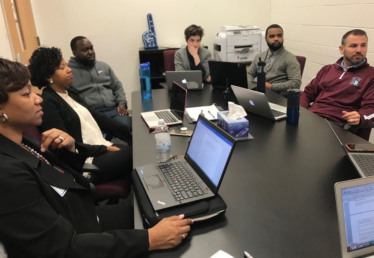 Coaches from the School Empowerment network including Carrmilla Young, left, and Jessica Westermann, center, huddle with Mumford Academy Principal Nir Saar, right, and his top leadership staff as part of a Team Fellows program that aims to push good schools to get better.