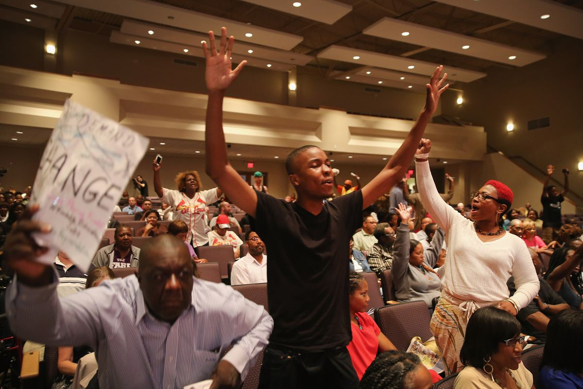 Ferguson residents protest at a city council meeting.