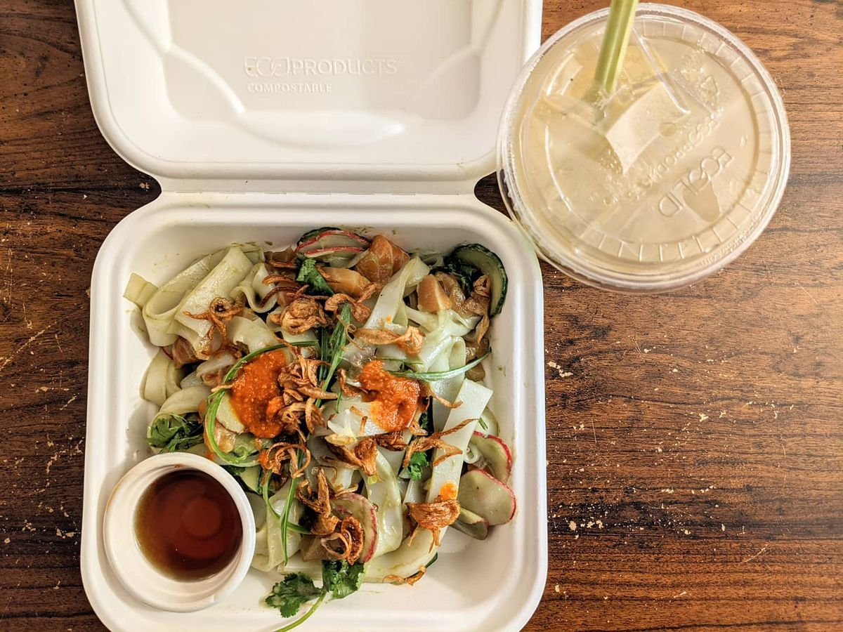 Overhead view of a white styrofoam container full of thick rice noodles, fried shallots, herbs, and pieces of cured salmon. It sits on a wooden surface with a plastic cup of creamy iced coffee next to it.
