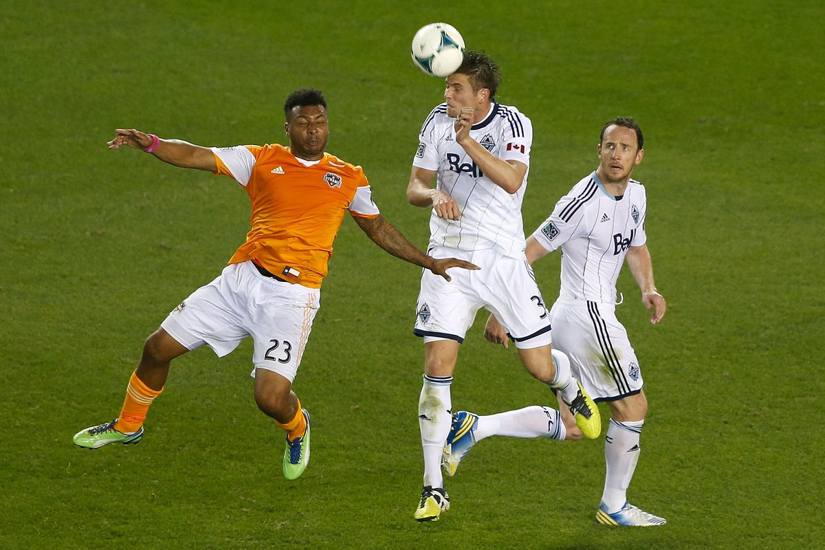 Vancouver Whitecaps center back Brad Rusin wins this aerial battle against the Houston Dynamo's Giles Barnes.
