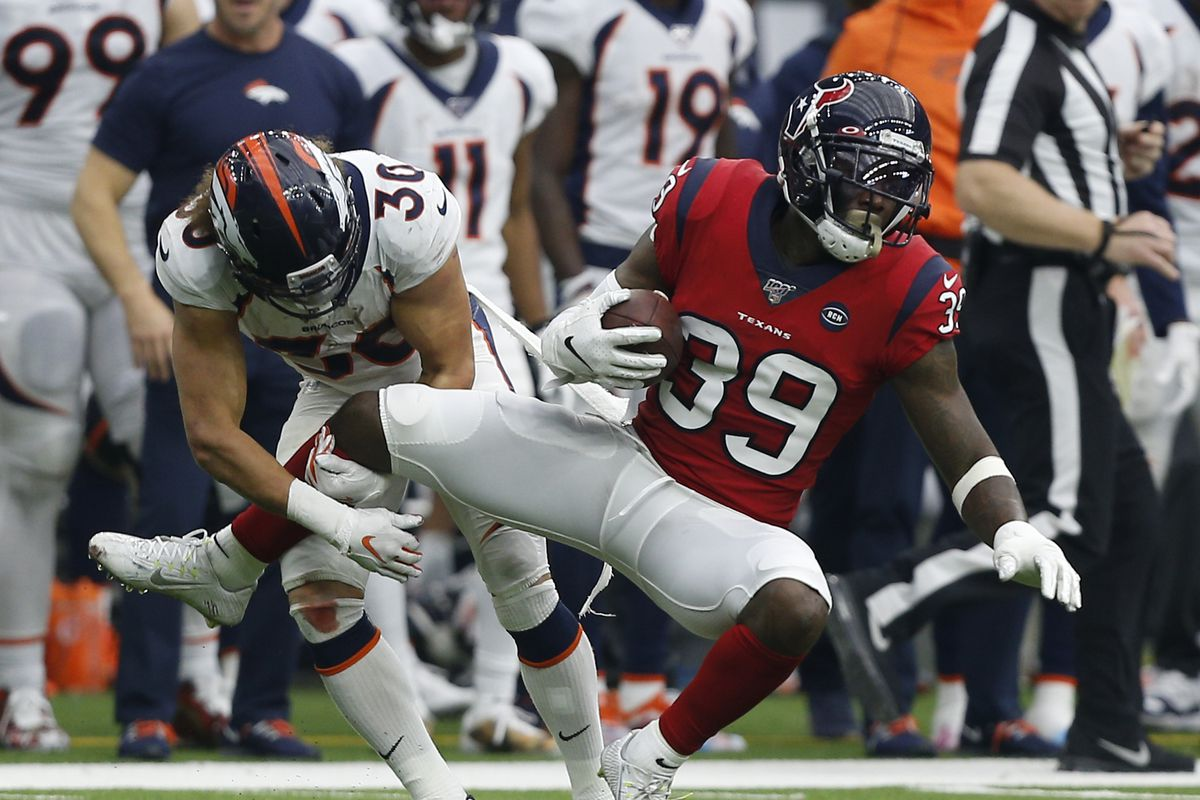 Tashaun Gipson of the Houston Texans is tackled by Phillip Lindsay of the Denver Broncos after an interception during the third quarter at NRG Stadium on December 08, 2019 in Houston, Texas.