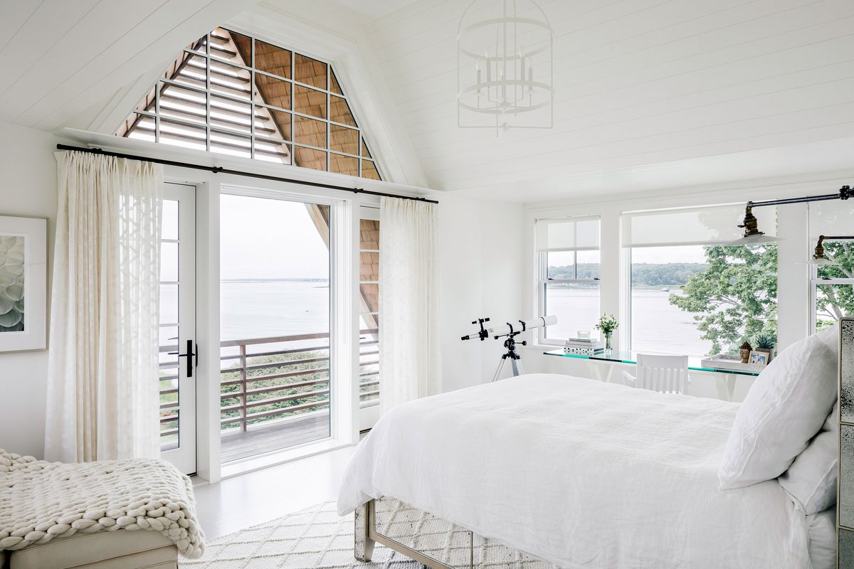 A bedroom has a bed that is surrounded by large windows that look out onto the water.