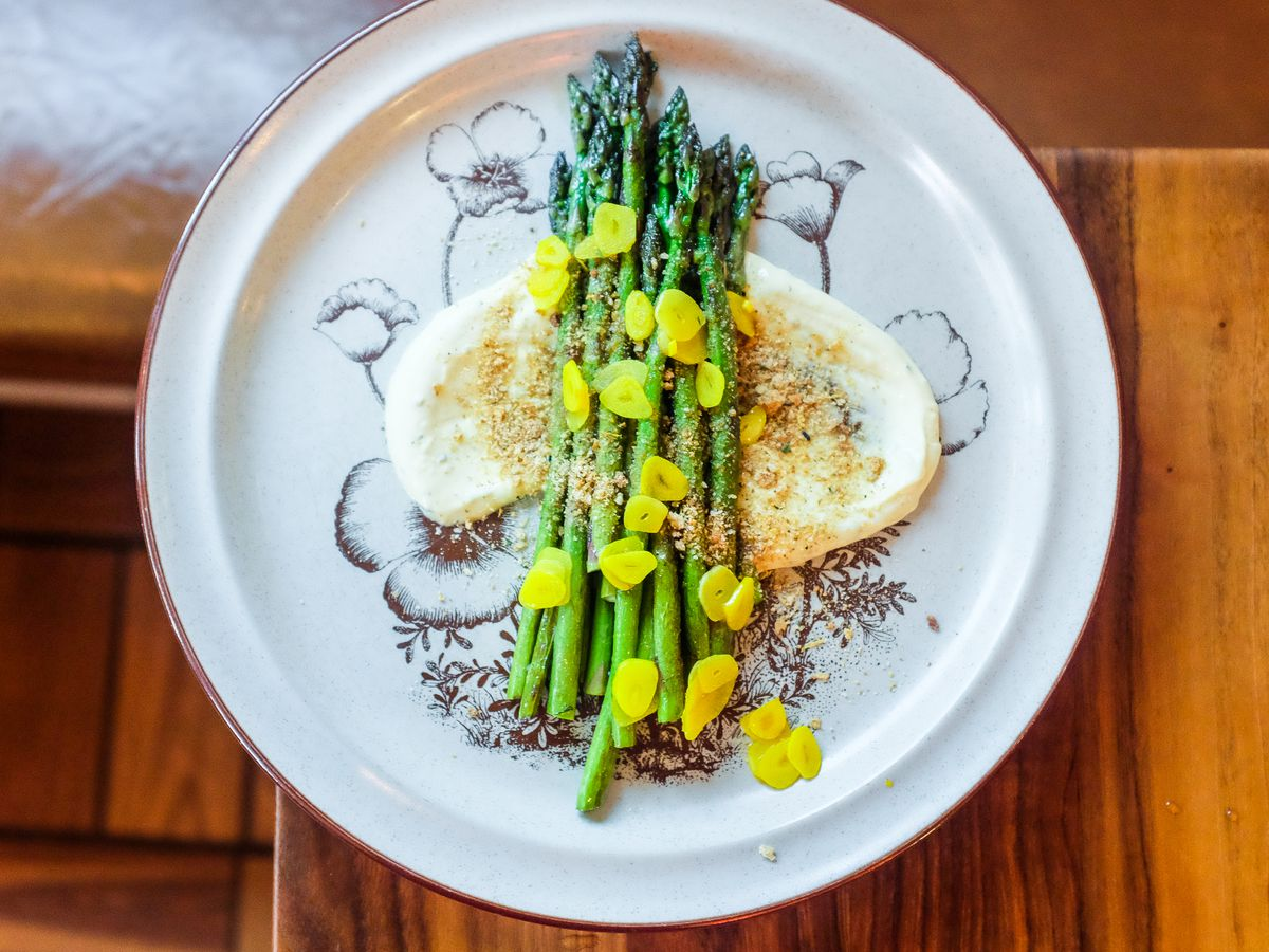 A plate of asparagus arranged over a creamy white sauce with some sort of crumble over the top and bright yellow sliced garlic.