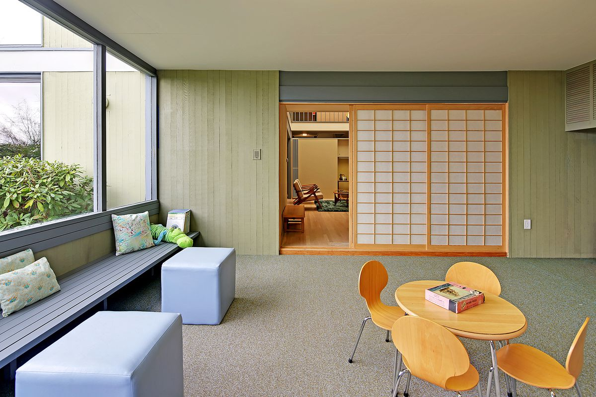 A playroom with a gray built-in bench on the left wall and large windows above. A shōji (paper) sliding door leads to another room in the back.