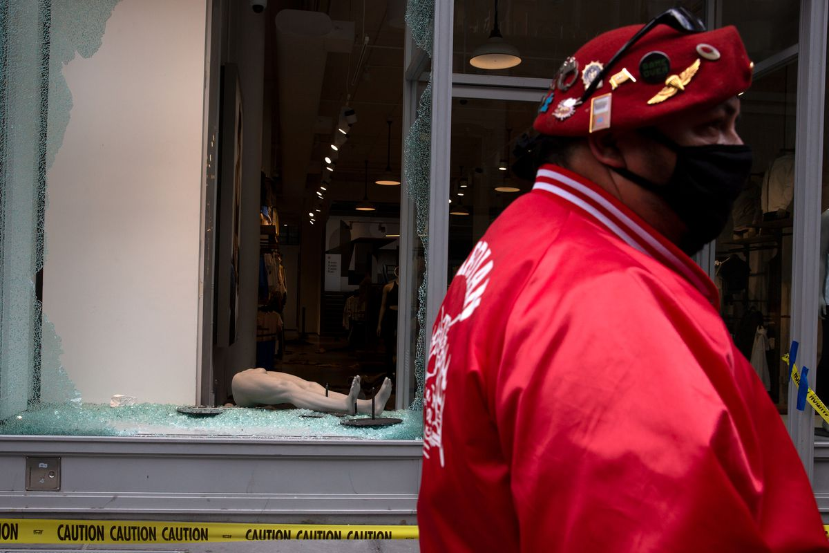 A Guardian Angel looks over damage to SoHo businesses.