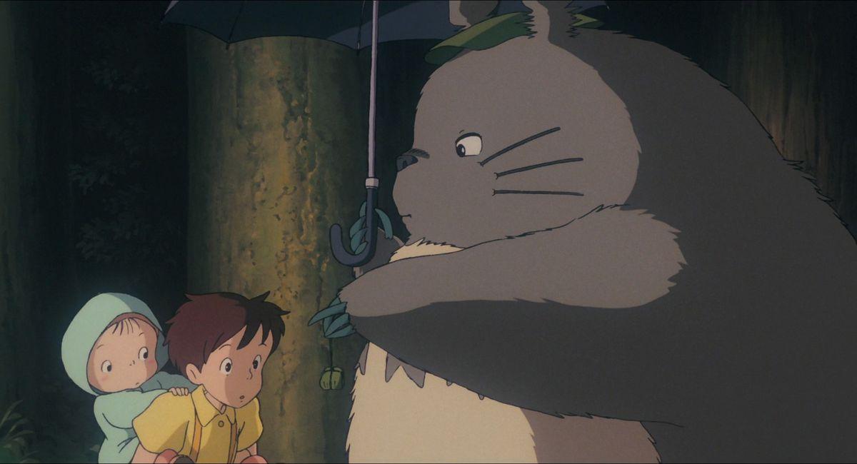 Totoro hands Satsuki and Mei a bundle of acorns