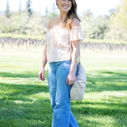 Quinta Gaines embraces the 70s trend with an off-the-shoulder top and wide-leg jeans.
