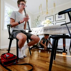 Peter Larsen practices his clarinet as his brother George hides under the table while playing hide-and-seek with mom Natalie at their home in Millcreek on Wednesday, Sept. 16, 2020.