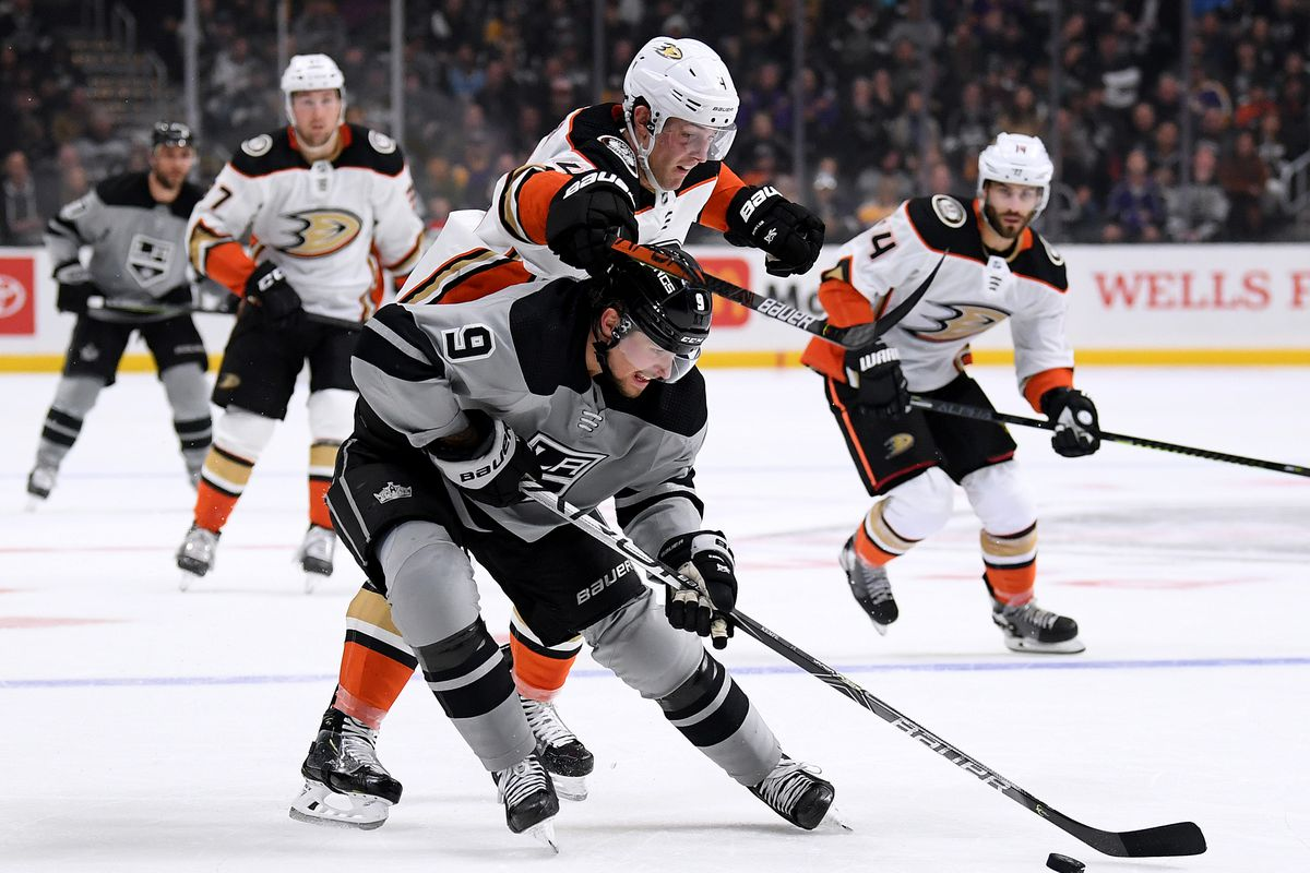 LOS ANGELES, CALIFORNIA - FEBRUARY 01: Adrian Kempe #9 of the Los Angeles Kings stick handles under Cam Fowler #4 of the Anaheim Ducks during the second period at Staples Center on February 01, 2020 in Los Angeles, California.