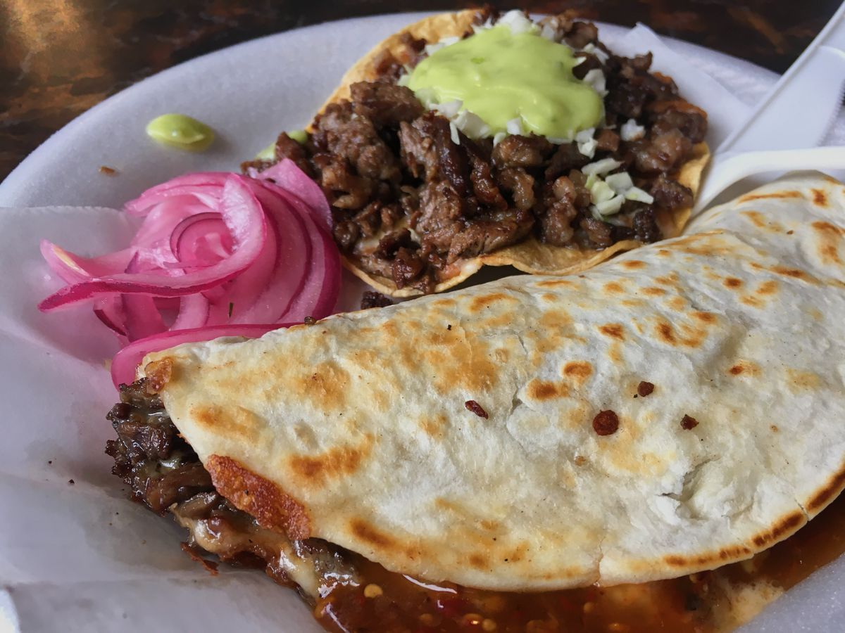 A taco molote and a vampiro sit next to a pile of pickled red onion on a styrofoam plate at Triángulo Dorado.