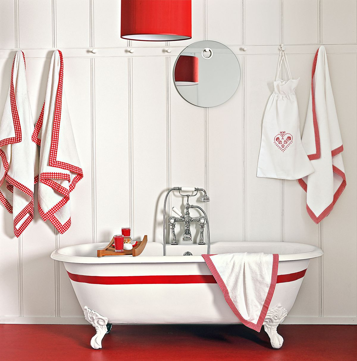 White paneled bathroom walls, red linoleum floors, and white bathtub with red stripe running across it.
