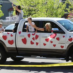 A familiy waves and cheers as they drive past residents The Ridge Cottonwood senior living center in Holladay during a Mother's Day parade on Saturday, May 9, 2020.